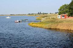 Urlaubsidylle auf der Insel Poel - Mecklenburg Vorpommern. Boote liegen am Steg - Holzhütte am Wasser.