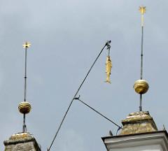 Giebelspitzen vom Rathausgebäude in Frankfurt/Oder; goldene Kugeln mit Stern und Fisch an der Angel.
