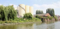 Silos und Lagergebäude am Ufer vom Neuhöfer Kanal in Hamburg Wilhelmsburg - wildes Gebüsch und Weiden wachsen am Wasser des Kanals.