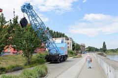 Promenade entlang der Oder in Frankfurt, Eisenbahnkran auf Schienen im ehemaligen Hafengebiet der Stadt.