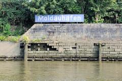 Kaimauer bei Niedrigwasser - blaues Schild Moldauhafen im Hamburger Stadtteil Kleiner Grasbrook.