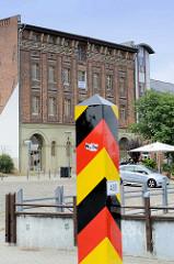 Grenzpfahl in den deutschen Farben schwarz, rot, gold am Ufer der Oder in Frankfurt - im Hintergrund ein historischer Warenspeicher.