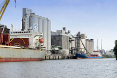 Industrieanlagen / Silos mit Frachtschiffen am Neuhofer Kanal in Hamburg Wilhelmsburg.
