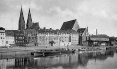 Historische Ansicht der Stadt Frankfurt/Oder, Blick zum Hafen; das Binnenschiff Landsberg Dampfmaschine, hoher Schornstein liegt am Kai. Daneben eine Kaianlage mit Arbeitskran auf Schienen, dahinter die Franziskaner-Klosterkirche sowie die Doppelt