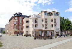 Kubische Architektur einer Pension am Ufer der Oder in Frankfurt, dahinter Gründerzeitgebäude.