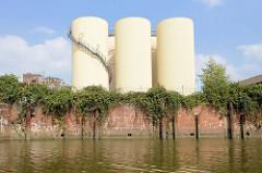 Alte Kaimauer mit Ziegelsteinen und wild wachsendes Gebüsch am Kanalufer vom Neuhöfer Kanal in Hamburg Wilhelmsburg - hohe runde Silos mit Treppe am Ufer.