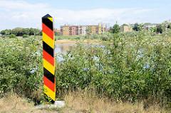 Grenzpfahl in den deutschen Farben schwarz-rot-gold am Ufer der Oder in Frankfurt; am gegenüberliegenden Ufer des Flusses Wohnhäuser in Słubice.