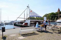 Fischverkauf vom Kutter am Hafen von Kirchdorf auf der  Insel Poel - Mecklenburg Vorpommern; im Hintergrund die Spitze vom Kirchturm der