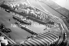 Luftaufnahme vom Hamburger Petroleumhafen auf  Hamburg Waltershof; ein Tankschiff  liegt am Löschplatz - Öltanks in unterschiedlichen Größen sind am Ufer. Rechts oben ein Ausschnitt vom Köhlbrand.