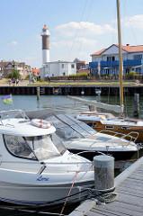Sportboothafen in Timmendorf auf der Insel Poel - Mecklenburg Vorpommern; Boote liegen am Steg - im Hintergrund der Leuchtturm.