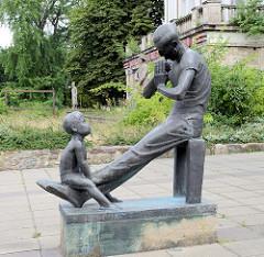 Kunst im öffentlichen Raum, Frankfurt/Oder; Bronzeskulptur Mundharmonika Spieler/Vater mit Sohn - Bildhauer  Hans-Detlev Hennig, 1987.