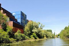Containerlager am Ufer vom Jaffe David Kanal in Hamburg Wilhelmsburg - das Ufer ist mit Weiden und Sträuchern dicht bewachsen.