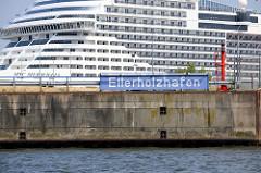 Blaues Schild / Hafenschild Ellerholzhafen im Hamburger Hafenstadtteil Steinwerder - im Hintergrund das Kreuzfahrtschiff MSC Meraviglia im Kaiser-Wilhelm-Hafen.