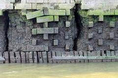 Kaimauer am Moldauhafen im Kleinen Grasbook; das Niedrigwasser legt das Holzfundament und Reste einer Ziegelmauer frei - in breite Risse kann Wasser eindringen.