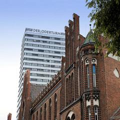 Giebel der Backsteinarchitektur der ehemaligen kaiserlichen Oberpostdirektion in der Lindenstraße von Frankfurt/Oder. Das denkmalgeschützte Gebäude wurde 1902 errichtet.  Im Hintergrund das markante Hochhaus Der Oderturm.