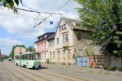 Baufälliges und renoviertes Wohnhaus - fahrende Straßenbahn in der Herbert-Jensch-Straße von Frankfurt / Oder.