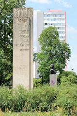 """Stele vom Karl Marx Denkmal an der Karl-Marx-Straße in Frankfurt/Oder; aufgestellt 1968. Inschrift """"Die Theorie wurde zur materiellen Gewalt""""; dahinter die Büste von Marx."""