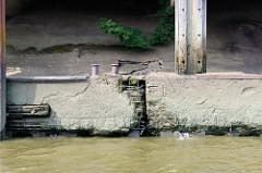 Fundament eines Lagerhauses am Moldauhafen in Hamburg Kleiner Grasbrook; die Eisenarmierung der Kaimauer ist teilweise freigelegt.