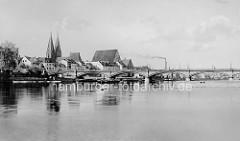 Alte Fotografie  von der Stadtbrücke über die Oder bei Frankfurt; die 264 m lange Bogenbrücke wurde 1895 erbaut. Im Hintergrund Kaianlagen am Fluss sowie die Doppeltürme der Friedenskirche und das hohe Dach vom Franziskaner Kloster-Kirche.