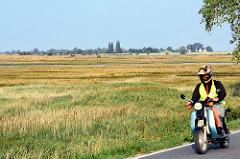 Wiesen auf der Insel Poel - Mecklenburg Vorpommern; Motorradfahrter in Fahrt.