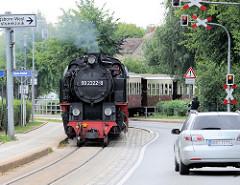 Die Bäderbahn Molli fährt in die Bahnstation Kühlungsborn-Mitte ein - die Straße ist mit roten Ampeln gesperrt. Der Zug wird von der Dampflok 992322-8 gezogen.