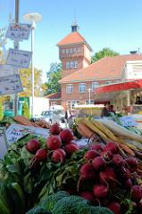 Marktstand mit Gemüse / Radischen auf dem Wochenmarkt in Hamburg Alsterdorf - im Hintergrund das historische Küchengebäude der Alsterdorfer Anstalten, das unter Denkmalschutz steht.