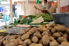 Wochenmarktstand mit Obst und Gemüse auf dem Wochenmarkt vom Winterhuder Marktplatz  im Hamburger Stadtteil Winterhude; im Vordergrund festkochende Kartoffeln Linda.