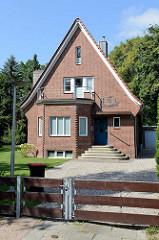 Einzelhaus mit Satteldach und einem Balkon in auf dem Erker - Wohnhaus mit Ziegelfassade im Hamburger Stadtteil Wellingsbüttel.