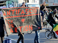 """Protestdemonstration gegen die rechtsgerichtete Kundgebung """"Merkel muss weg"""" in Hamburg. Demonstrationszug mit Transparent."""