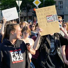 """Protestdemonstration gegen die rechtsgerichtete Kundgebung """"Merkel muss weg"""" in Hamburg. Demonstrationszug mit Fahne und handgeschriebenem Plakat."""