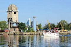 Siloanlagen eines Kais mit Schüttgut an der Westoder im Stettiner Hafen; ein Sportboot fährt flussabwärts.