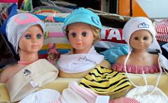 Marktstand mit Kleidung auf dem Wochenmarkt in Hamburg Alsterdorf - Kinderkopfe aus Plastik tragen bunte Mützen.