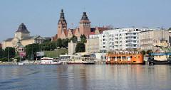 Hafenpanorama von Stettin, Wohnhäuser am Ufer der Oder;  Ausflugsschiffe liegen am Kai im Hintergrund die historische Architektur vom  Regierungsgebäude der Provinz Pommern sowie dem Nationalmuseum.