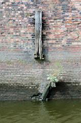 Alte Kaimauer / Brückenfundament der Eisenbahnbrücke über den Tidekanal in Hamburg Billbrook. Ein alter Holz - Streichdalben hat früher die Ziegelwand vor Beschädigung geschützt - jetzt ist er zerbrochen Kraut wächst aus dem vermodertem Holz.