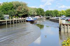 Blick auf die Krückau im Elmshorner Hafen bei Ebbe - das Hafenbecken ist größtenteils trockengefallen. Im Hintergrund das Binnenmotorfrachtschiff Klostersande, das  zwischen 1968 und 2000 für die Köllnflockenwerke  Getreide zwischen dem Hamburger Haf