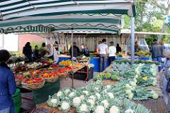 Marktstand mit frischem Gemüse auf dem Wochenmarkt Tibarg im Hamburger Stadtteil Niendorf. Blumenkohl, Kohlrabi und Brokkoli sind auf einem Tisch ausgebreitet, verschiedene Paprikasorten liegen in  Weidenkörben.