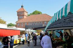 Markttreiben / Marktstände  auf dem Alsterdorfer Marktplatz im Hamburger Stadtteil Alsterdorf. Im Hintergrund das historische Küchengebäude der Alsterdorfer Anstalten, das unter Denkmalschutz steht.