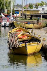 Fischereihafen in in Ziegenort / Trzebież; kleine Holzboote liegen am Kai des Hafenbeckens.