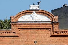 Giebel eines Backsteingebäudes Stettiner Hafen mit Stuckrelief.