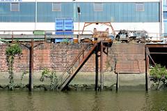 Ufermauer mit Ziegeln und verrosteter Eisentreppe im Querkanal von Hamburg Steinwerder.
