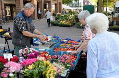 Marktstand mit frischen Tomaten und Blumensträußen auf dem  Wochenmarkt in Hamburg Eidelstedt.