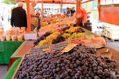 Marktstand mit Obst / Obststand auf dem Wochenmarkt in Hamburg Eidelstedt - Elbgaustraße; im Vordergrund ein Berg von frischen Zwetschen, Zwetschgen - dahinter Beeren und Weintrauben.