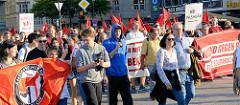 """Protestdemonstration gegen die rechtsgerichtete Kundgebung """"Merkel muss weg"""". Demonstrationszug mit Transparenten und roten Fahnen auf dem Hamburger Jungfernstieg."""