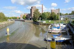 Die Krückau in Elmshorn bei Niedrigwasser / Ebbe;  nur ein schmales Rinnsal zeigt die Fahrrinne an; die Sportboote sind trockengefallen und liegen im Schlick - im Hintergrund die Industriearchitektur der Köllnflockenwerke.