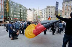 """Ein Fotograf sucht ein fotogenes Motiv auf der rechtsgerichteten Kundgebung """" Merkel muss weg """"; er fotografiert die Deutschlandflagge."""