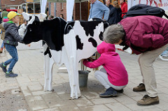 An einer Holzkuh können Kinder das Melken auf dem Kartoffelfest vom Gut Wulksfelde üben.