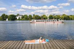 Eine junge Frau liegt auf einem Holzsteg an der Hamburger Außenalster in der Sonne und liest; ein Fahrgastschiff der als der Flotte fährt vorüber - im Hintergrund Wohnhäuser der Bellevue in Hamburg Winterhude.