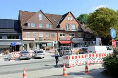Baustelle in der Rolfinckstraße, Hauptgeschäftstraße in Hamburg Wellingsbüttel - die Straße ist halbseitig gesperrt.
