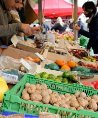 Wochenmarkt im Hamburger Stadtteil Eimsbüttel / Grundstraße - Marktstand mit Obst und Gemüse, im Vordergrund frisch geerntete Walnüsse.