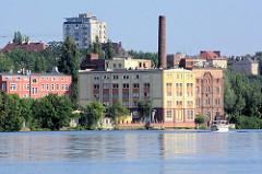 Alte Lagerhäuser am Ufer der Westoder in Stettin, im Hintergrund Hochhäuser.
